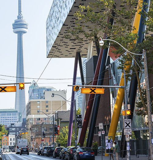 Toronto, Сanada - September 5, 2015: Low-angle view of the modern expansion of the Sharp Centre for Design at the campus of the Ontario College of Art (OCAD) in downtown Toronto, with the CN tower in the background. The building consists of an elevated white and black box supported by a series of multicolored inclined pillars.