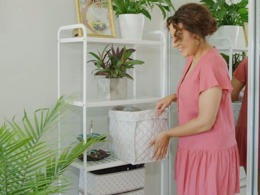 Natasha shows off her storage bins in her rental apartment